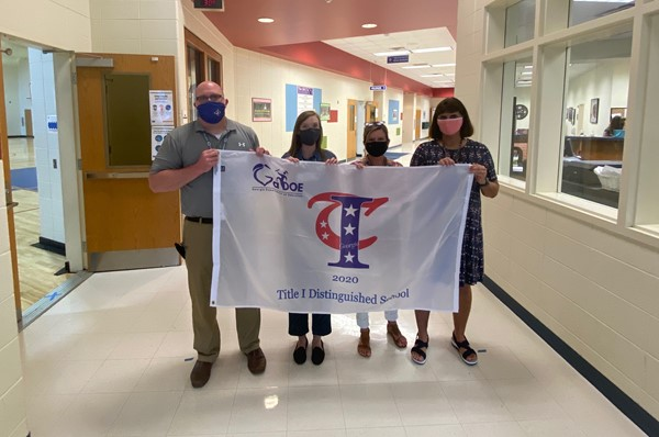 Principal Chris Whitworth, Lead Instructional Teacher Samantha Barrett, Data Coordinator Lori Alexander, and AP Mrs. Carol Ann Knight showcase the 2020 Title I Distinguished School Award banner.